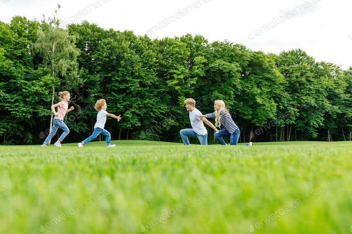 happy young family with two kids playing on green meadow in park