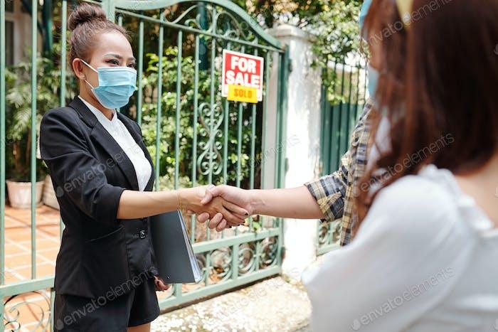 Агент по недвижимости приветствует молодых клиентов