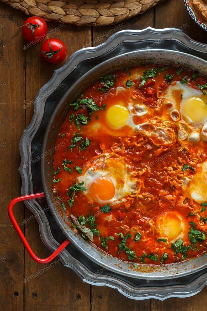 Spicy shakshuka in a pan with parskey , bread and hummus, close view