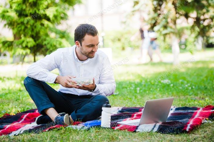 Junger und attraktiver Mann entspannt sich im Park zur Mittagszeit