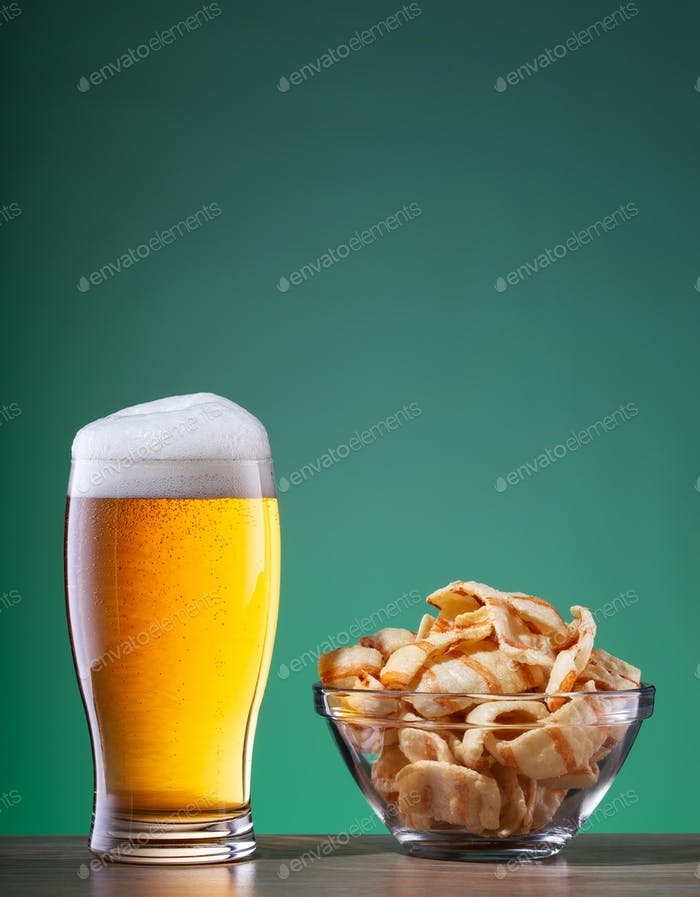 Light beer with foam in glass and snacks in transparent plate on green background