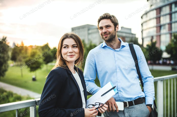 A young businessman and businesswoman standing on a bridge.