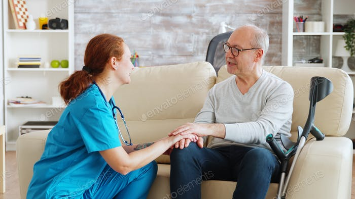 Female nurse talking and taking care of old disabled man sitting on the sofa