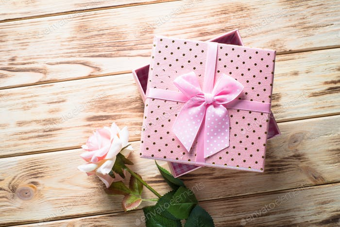 Present box and flower on wooden table.