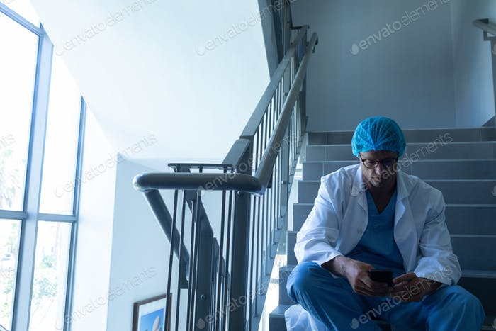 Front view of Caucasian male surgeon using mobile phone while sitting on stairs at hospital