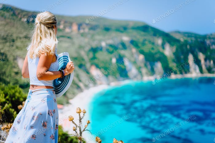 Young woman in front of Petani beach Kefalonia admiring highly excited picturesque panorama of