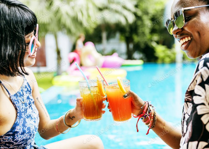Hands holding juice glasses by the pool summer time