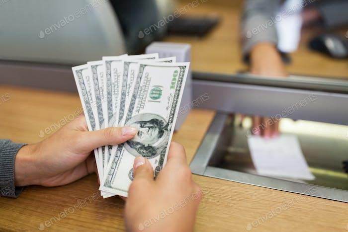 Hände mit Geld bei Bankbüro oder Tauscher