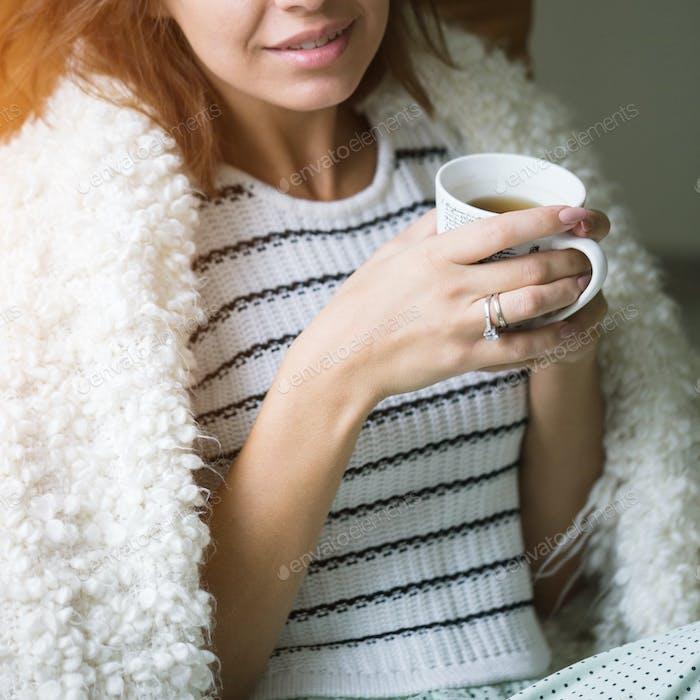 Junges schönes Mädchen mit einer Tasse Kaffee sitzt auf der Couch zu Hause.