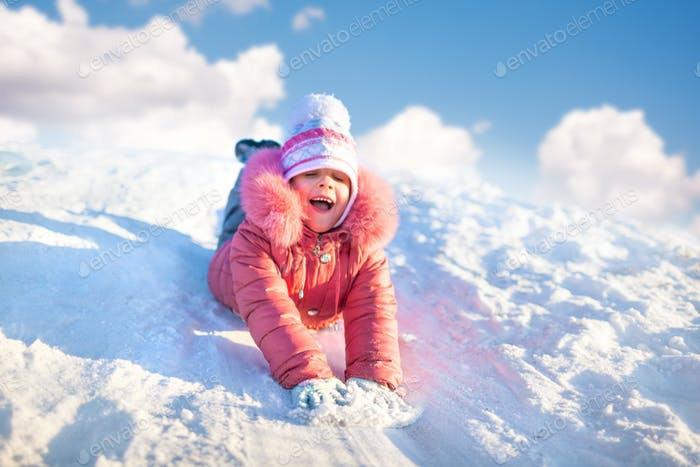 Small girl in winter clothing riding downhill on snow with hands forward