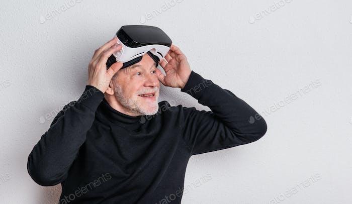 Porträt eines fröhlichen Senior Mannes mit VR-Brille in einem Studio.