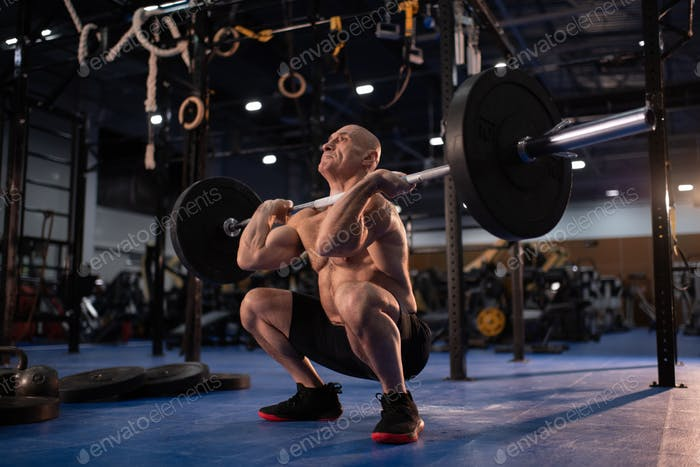 Muscular male athlete squatting with heavy barbell