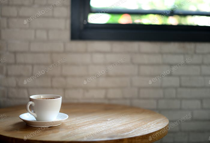White coffee mug on a wooden table And white brick background.