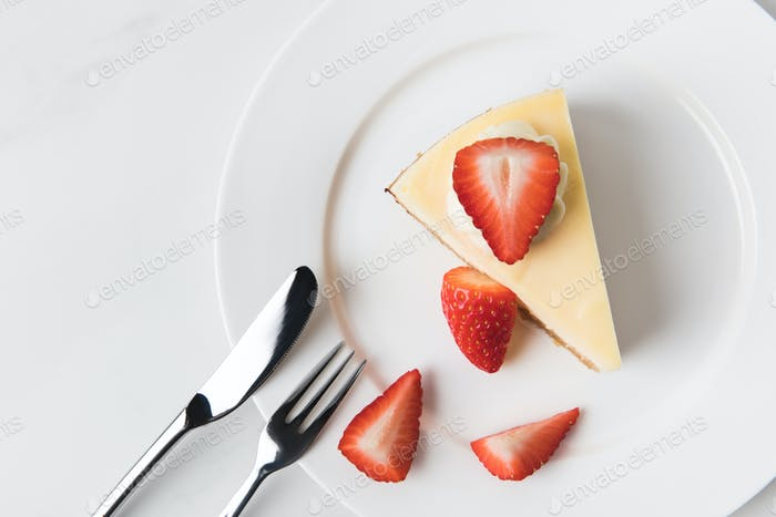 Plate with cheesecake surrounding by sliced strawberries