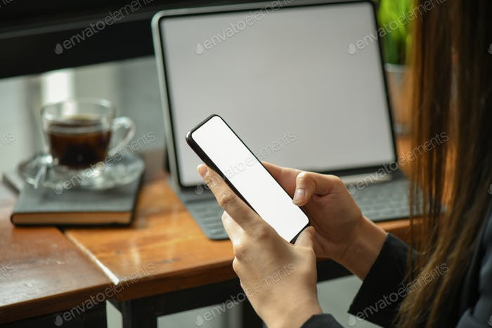 Businesswomen using on a blank screen smartphone in the office.