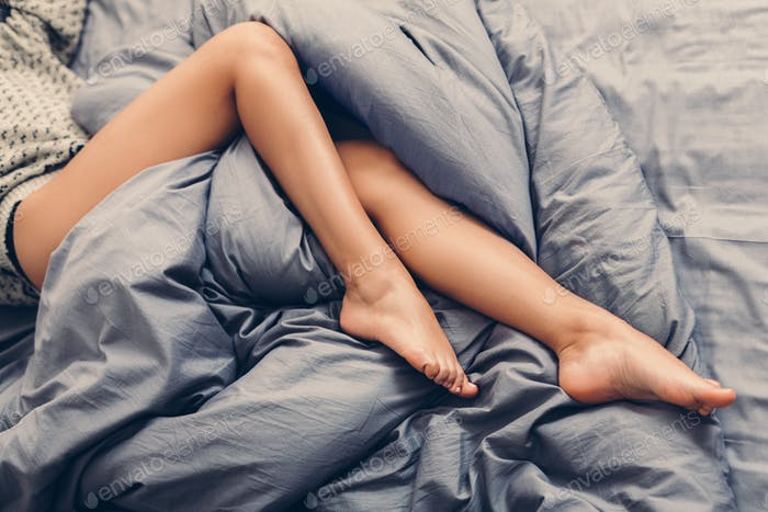 Naked female legs lying on bed top view