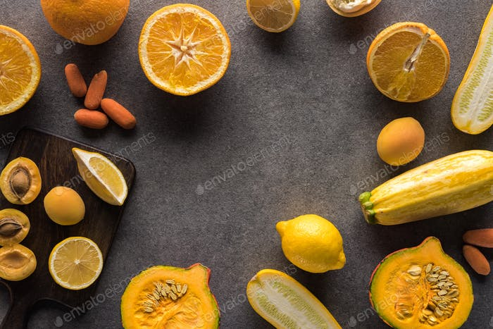 Top View of Yellow Fruits And Vegetables And Wooden Cutting Boards on Grey Background