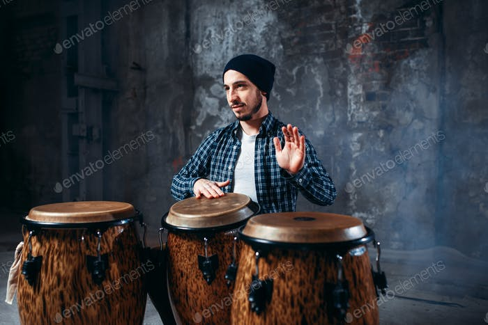 Drummer playing on wooden bongo drums, beat rhythm