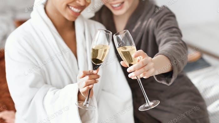 Geschnitten von zwei multiethnischen spa freundinnen halten Gläser Champagner