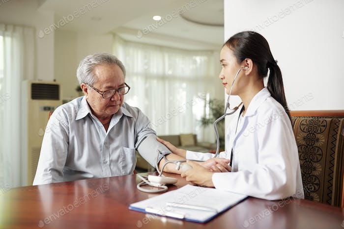 Nurse examining the patient at home