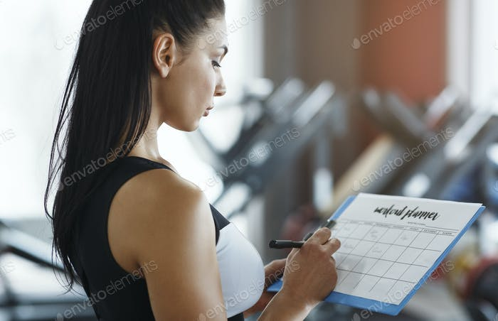 Personal trainer with clipboard making workout plan in gym