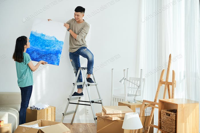 Young couple hanging picture in new flat