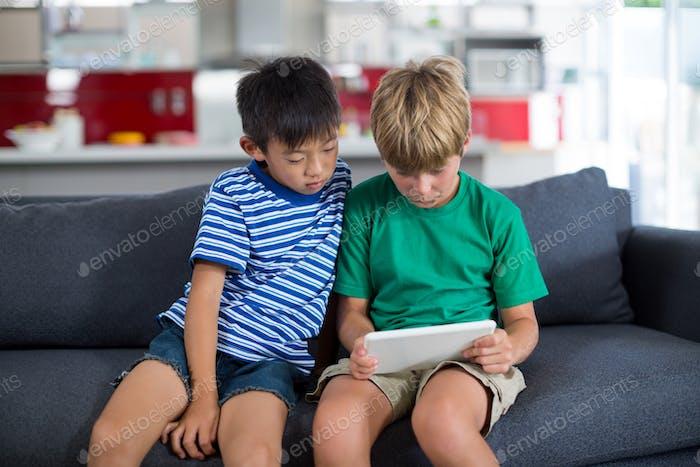 Siblings using digital tablet in living room