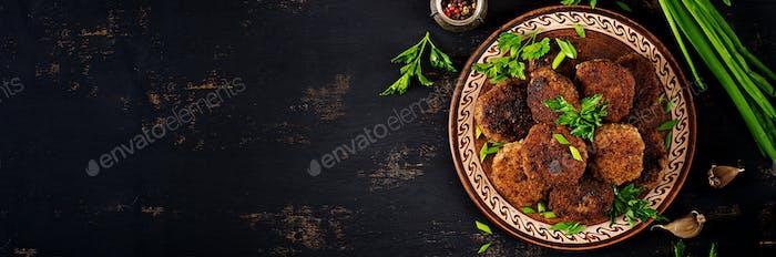 Saftige leckere Fleischkoteletts auf einem dunklen Tisch. Russische Küche. T