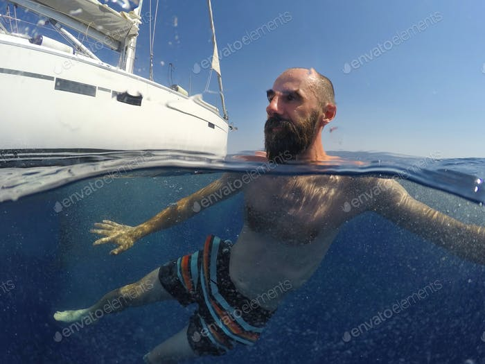 Young man swiming near the yacht. Underwater photo