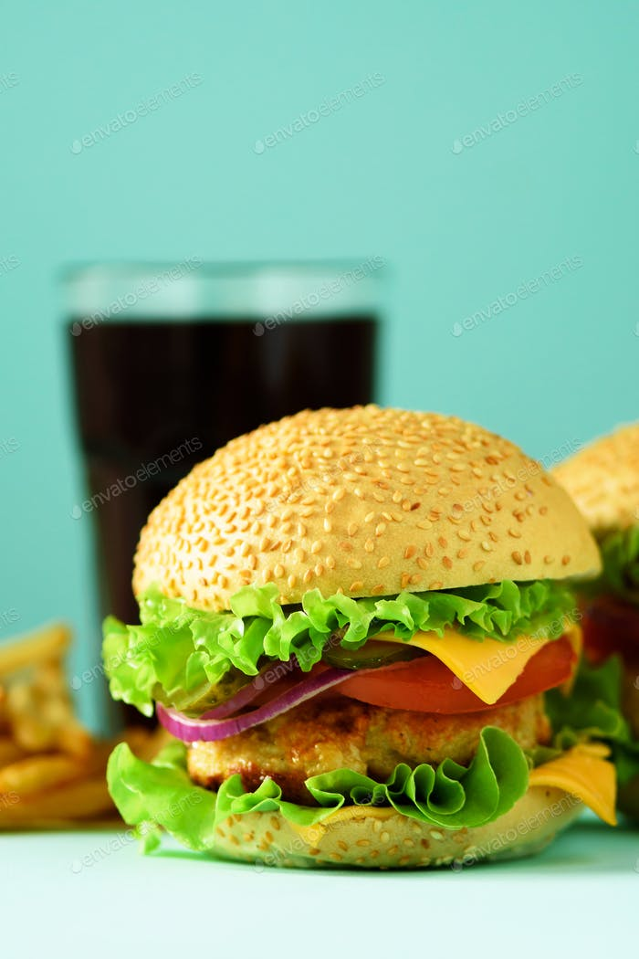 Fast food concept. Juicy homemade hamburgers on blue background. Take away meal. Unhealthy diet
