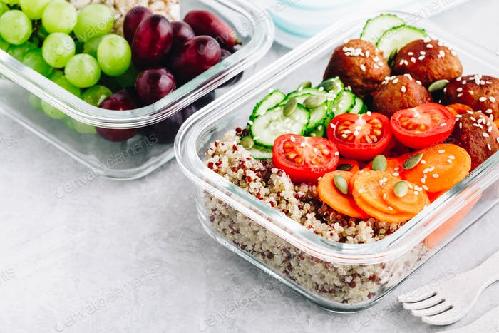 Meal prep lunch box containers with quinoa, meatballs cucumbers, carrots and pumpkin seeds