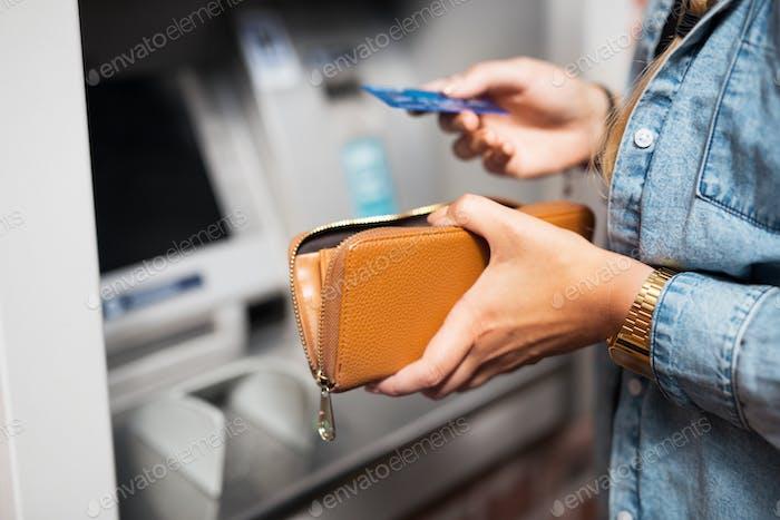 Frau Geld vom Geldautomaten abheben
