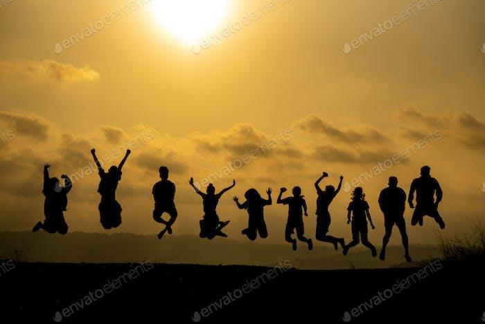 La silueta de un grupo de personas está celebrando el éxito en la cima de la colina.