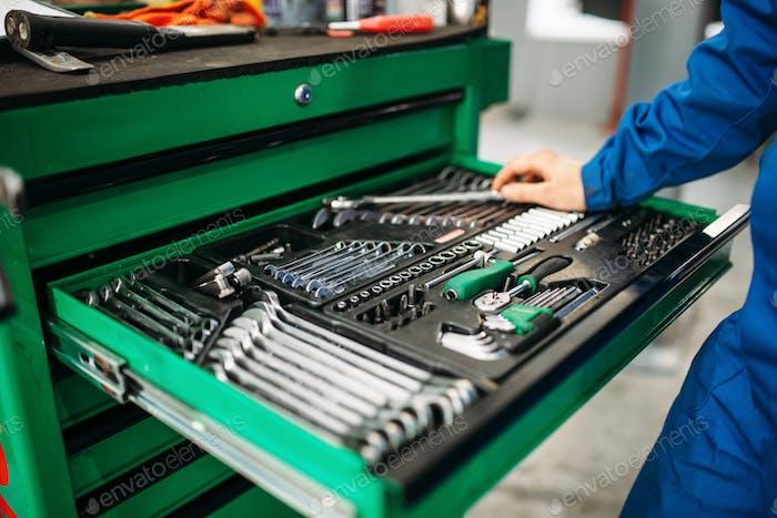 Repairman hand reaching for the tool box