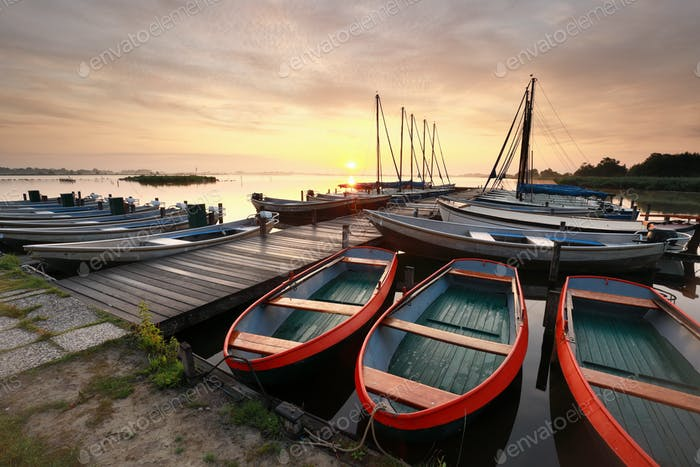 beautiful sunrise over lake with pier and yachts