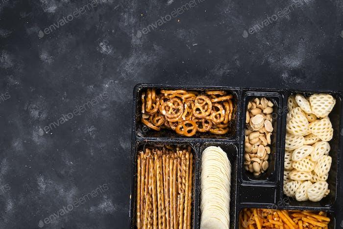 eine Vielzahl von Snacks auf der Box für Bier auf einem Beton schwarzen Tisch