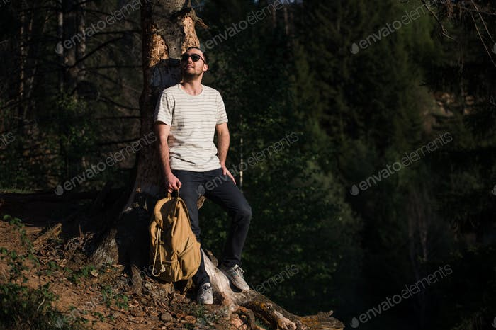 Handsome stylish young man wearing white t-shirt and sunglasses with backpack in his hand is