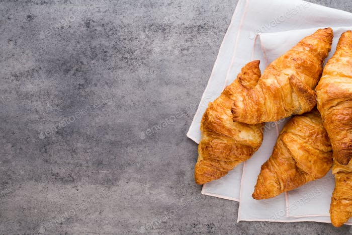 Tasty buttery croissants on old graye table.