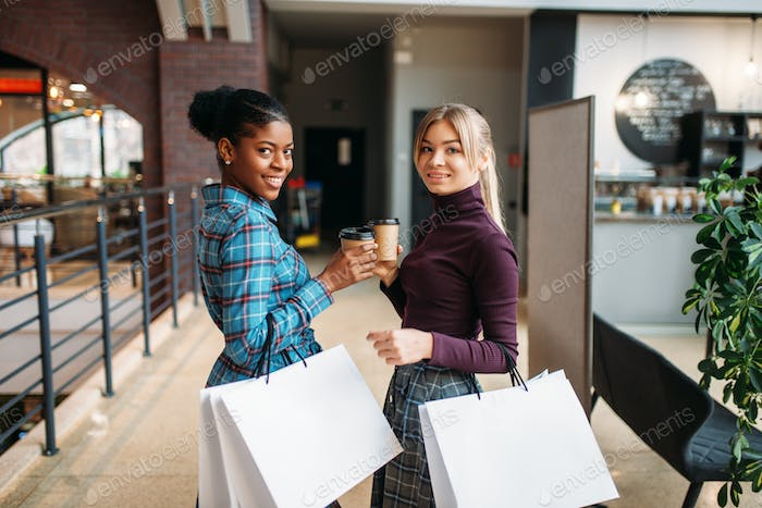 White and black female customers with shopping bag