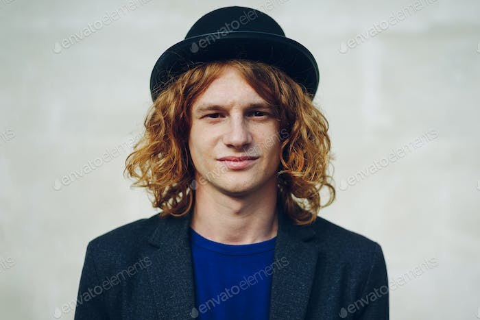 Fashion portrait of young reddish curly man