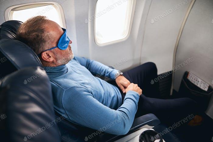 Male entrepreneur in the sleep mask sleeping peacefully