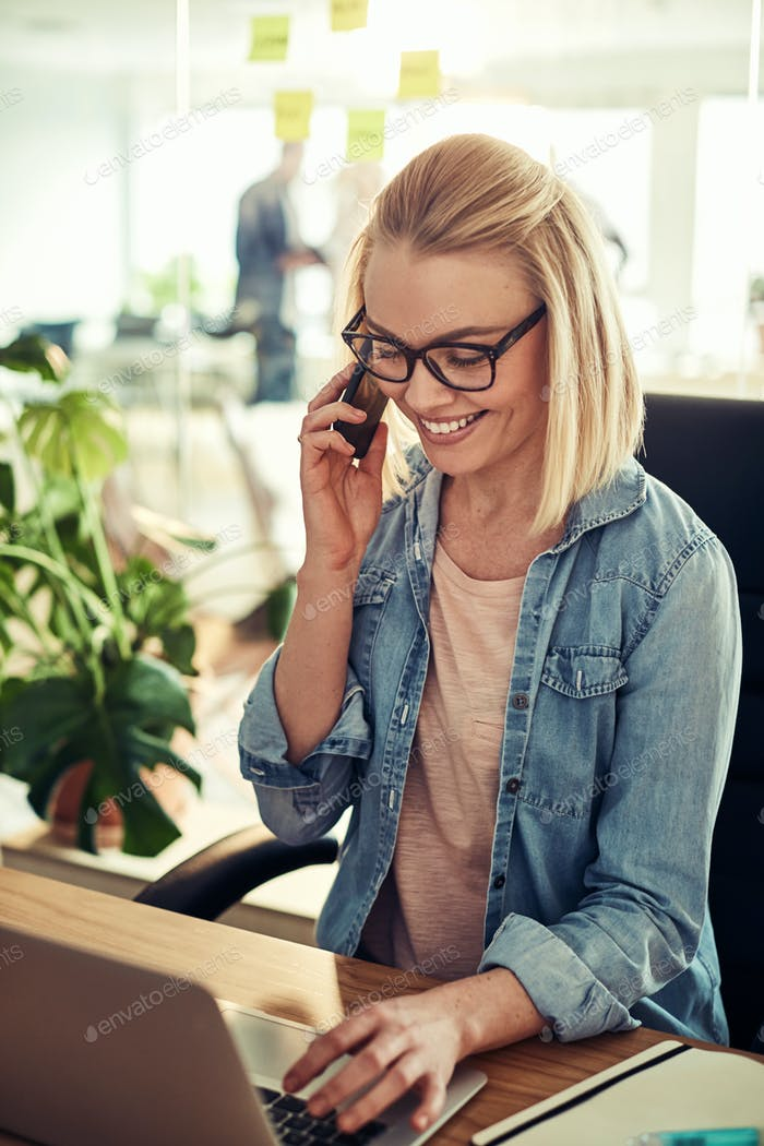 Smiling businesswoman sitting in an office talking on a cellphone