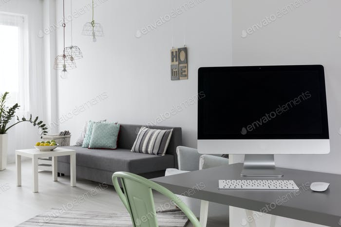 Grey desk with computer in modern living room