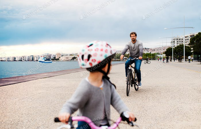 Father and small daugther with bicycles outdoors cycling on beach