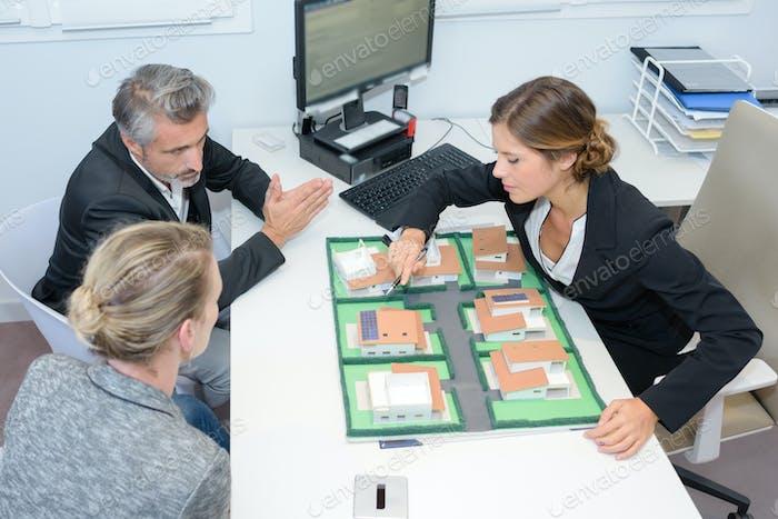 Agent und Paar diskutieren Immobilienvertrag Draufsicht