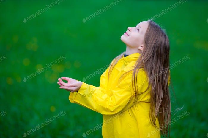 Kleines Mädchen im Regenmantel spielen in der regen im freien