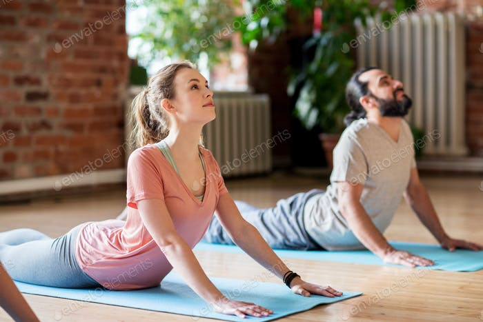 man and woman doing yoga cobra pose at studio