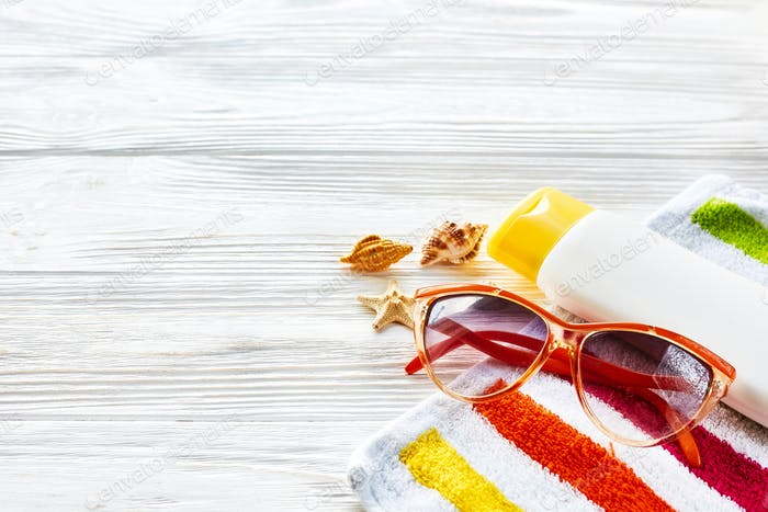 Colorful towel, sunglasses, yellow sunscreen and star shells