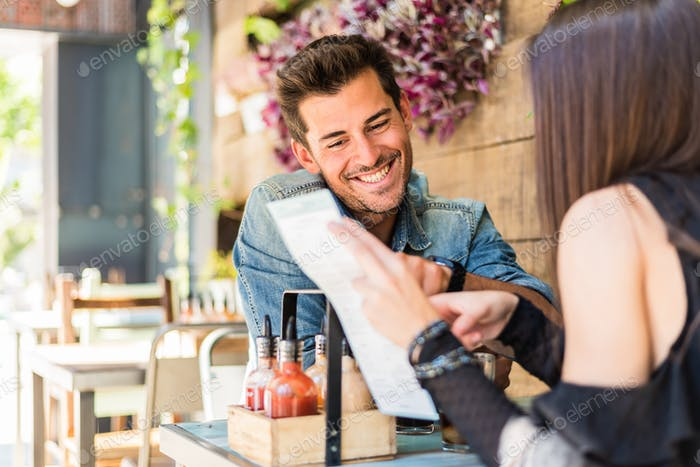 Happy young couple seating in a restaurant looking at the menu