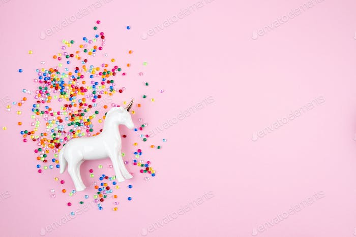 Flat lay with white unicorn and colorful glitter over the pink background. Magic surreal, fairy tale